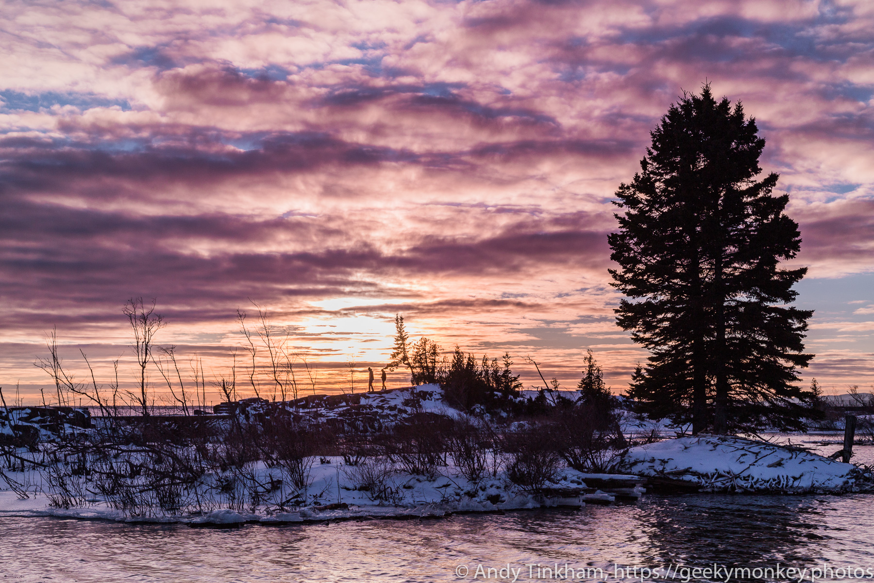 2 silhouetted people walk back on a snowy lake show under a purple and orange sunset